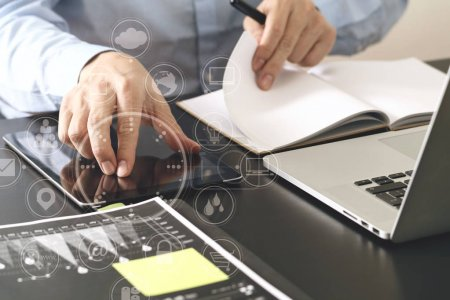 Photo for Close up of businessman working with smart phone and digital tablet and laptop computer  on wooden desk in modern office with virtual icon diagram - Royalty Free Image