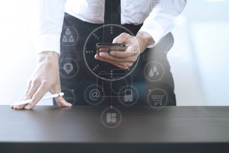 Photo for Close up of businessman working with smart phone on wooden desk in modern office with virtual icon diagram - Royalty Free Image