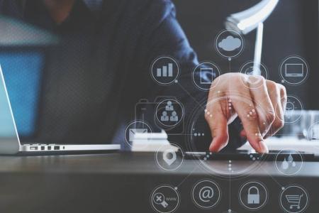 Photo pour Homme d'affaires utilisant une tablette numérique et un ordinateur portable et un document dans un bureau moderne avec un diagramme de réseau d'icônes graphiques d'interface virtuelle - image libre de droit