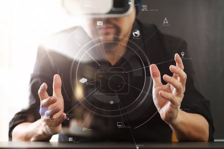 Photo for Businessman wearing virtual reality goggles in modern office with mobile phone using with VR headset with screen icon diagram - Royalty Free Image