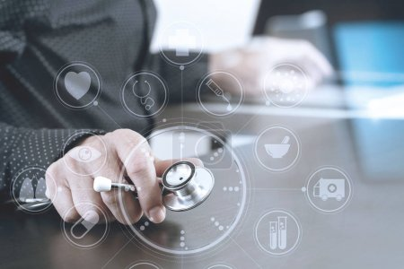Photo for Close up of smart medical doctor working with stethoscope and laptop computer on dark wooden desk with virtual icon diagram - Royalty Free Image