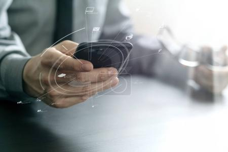 close up of businessman working with mobile phone and eyeglass o