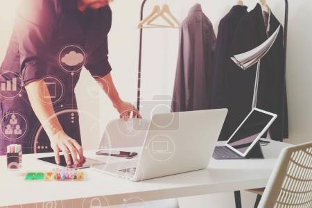 Fashion designer talking mobile phone and using laptop with digi