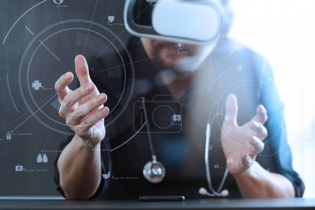 Photo for Smart doctor wearing virtual reality goggles in modern office with mobile phone using with VR headset with screen icon diagram - Royalty Free Image
