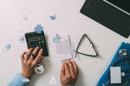 Foto de Vista superior de salud concepto de costos y honorarios. Mano del doctor smart utiliza una calculadora para los costes médicos en un hospital moderno con diagrama de icono de Vr - Imagen libre de derechos
