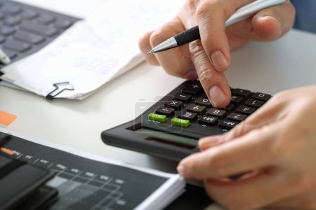 close up of businessman hand working with finances about cost an