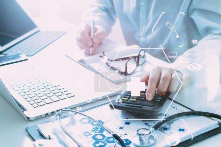 Photo pour La main du médecin intelligent a utilisé une calculatrice pour les coûts médicaux dans l'hôpital moderne avec diagramme icône VR - image libre de droit