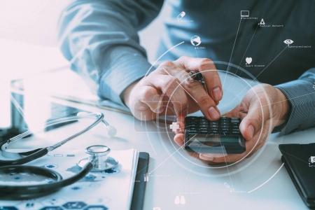 Foto de Concepto costos y honorarios médico. Mano del doctor smart utiliza una calculadora para los costes médicos en un hospital moderno con diagrama de icono de Vr - Imagen libre de derechos