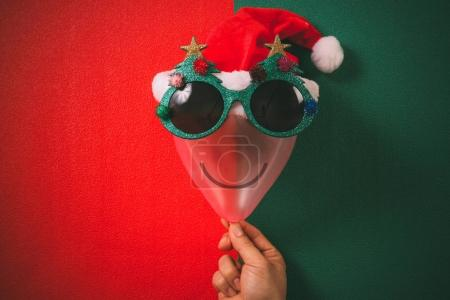 Hand holding Christmas glasses that decoration with Christmas tr