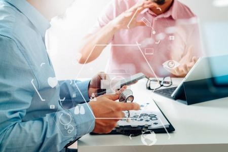 Medical doctor using mobile phone and consulting businessman pat