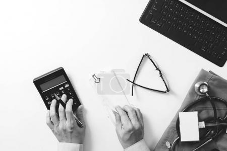 Foto de Vista superior de salud concepto de costos y honorarios. Mano del doctor smart utiliza una calculadora para los costes médicos en el hospital moderno, negro con blanco - Imagen libre de derechos