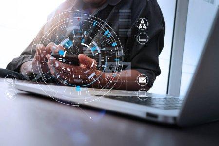 Photo pour Gros plan de l'homme d'affaires travaillant avec téléphone intelligent et tablette numérique et ordinateur portable sur un bureau en bois dans un bureau moderne avec un diagramme d'icône virtuelle - image libre de droit