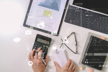 Photo for Top view of businessman hand working with finances about cost and calculator and latop with mobile phone on withe desk in modern office with VR icon diagram - Royalty Free Image