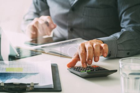 Photo pour Main d'homme d'affaires travaillant avec des finances sur le coût et la calculatrice et le loquet avec téléphone mobile sur le bureau withe dans un bureau moderne avec diagramme icône VR - image libre de droit