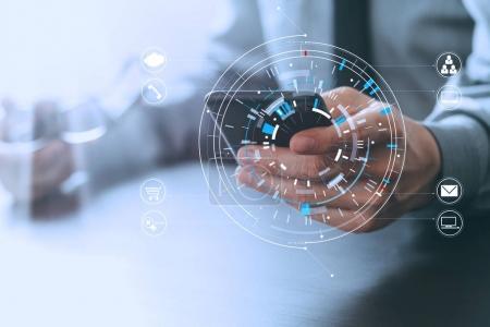 Foto de Primer plano del hombre de negocios que trabaja con el teléfono inteligente y la tableta digital y el ordenador portátil en el escritorio de madera en la oficina moderna con diagrama de icono virtual - Imagen libre de derechos
