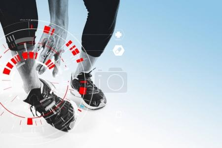 Athletic man touching foot due to sprain with VR medical scannin