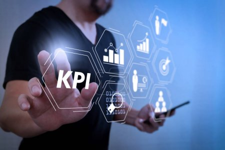 Photo for Key Performance Indicator (KPI) workinng with Business Intelligence (BI) metrics to measure achievement and planned target.Designer hand pressing an imaginary button,holding smart phone. - Royalty Free Image