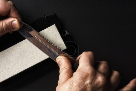 Photo for Sharpening a knife in your hand using the grindstone - Royalty Free Image