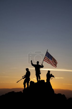 Photo for Three armed soldiers with American flag on the top of the mountain - Royalty Free Image