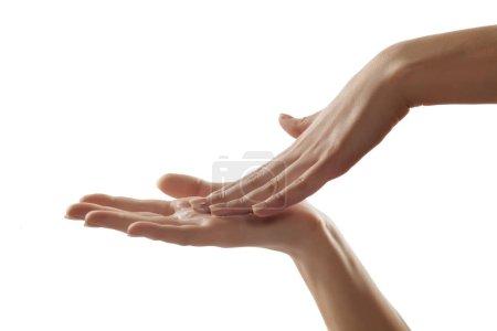Photo pour Gros plan des mains féminines appliquant de la crème pour les mains - image libre de droit