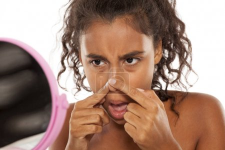 Photo for Young beautiful black woman squeezing pimples on her nose in front of a mirror - Royalty Free Image
