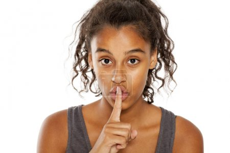 Photo pour Portrait d'une belle jeune femme à la peau foncée avec un doigt sur les lèvres sur un fond blanc. Concept de silence - image libre de droit