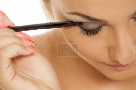 Photo pour Jeune femme appliquant ombre à paupières avec un pinceau - image libre de droit
