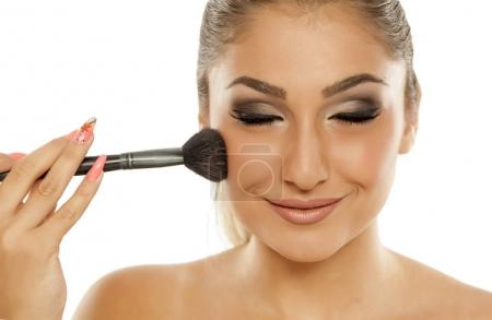 Young beautiful woman applying blush with a brush