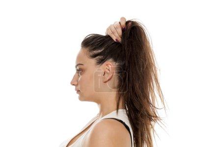 Zobrazení profilu mladé ženy drží vlasy rukou