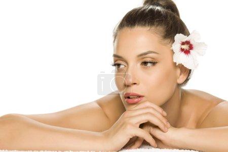 Photo pour Portrait sensuel d'une jeune et belle femme avec la fleur sur les cheveux, couchée sur un fond blanc - image libre de droit