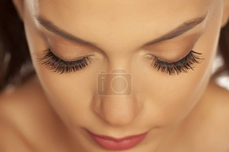 Photo pour Closeup of a young beautiful woman with closed eyes and eyelash extension on a white background - image libre de droit