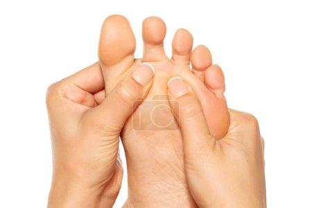 Frau massiert ihren schmerzhaften Fuß auf weißem Hintergrund