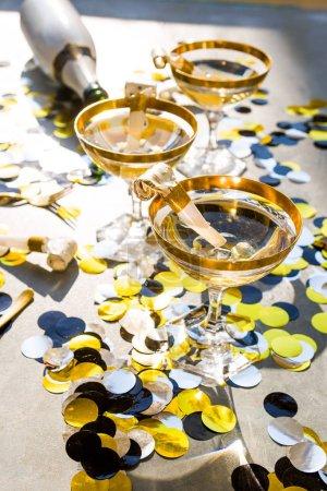 Photo pour Champagne party 2020 nouvelle année image conceptuelle, élégant verre de champagne avec une bouteille, vue sur le dessus, lumière dure, décoration de Noël, ombre forte . - image libre de droit