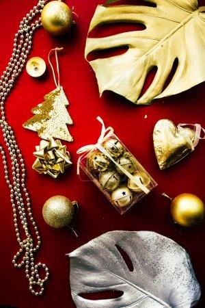 Photo pour Fête de Noël exotique, deux feuilles de monstère géantes peintes d'or et d'argent avec dcoration de Noël dorée sur fond rouge, vue de dessus, concept de luxe de Noël . - image libre de droit