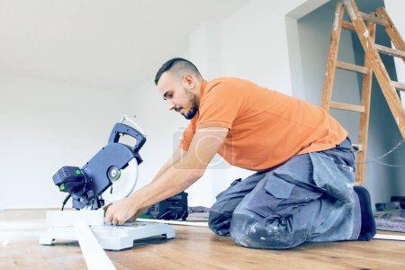 Foto de Trabajador cortando zócalos en una obra de construcción. Ponga el suelo de parquet - Imagen libre de derechos