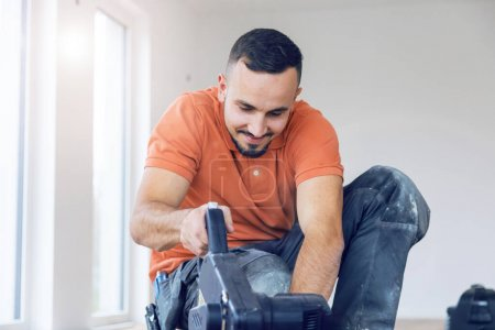 Foto de El joven con una cuchara vio cortar tablas de patinaje en una obra de construcción.. - Imagen libre de derechos