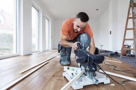 Photo pour Jeune homme avec une scie à découper les plinthes sur un chantier de construction . - image libre de droit