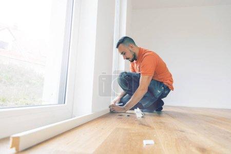Foto de Hombre enfocado cortando tablas de bordear en un sitio de construcción. Ponga el suelo de parquet - Imagen libre de derechos