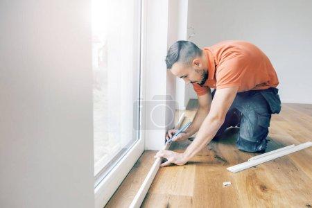 Foto de Hombre cortando zócalos en un sitio de construcción. Ponga el suelo de parquet - Imagen libre de derechos