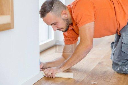 Foto de Vista lateral de las tablas de corte de hombre en una obra de construcción. Planta baja de parquet - Imagen libre de derechos