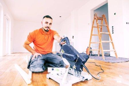 Foto de Jovencito con una cuchara vio cortar tablas de patinaje en una obra de construcción. Planta baja de parquet - Imagen libre de derechos
