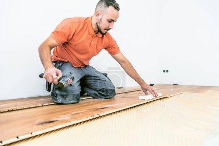 Foto de Joven trabajador masculino en obras de construcción. Planta baja de parquet - Imagen libre de derechos