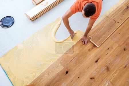 Foto de Vista aérea del trabajador instalando suelo de parquet en el sitio de construcción - Imagen libre de derechos