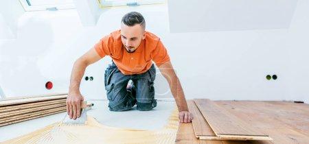 Foto de Trabajador que instala suelo de parquet en la obra - Imagen libre de derechos