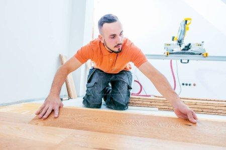Foto de Trabajador que instala piso de parquet en el sitio de construcción. Ponga el suelo de parquet - Imagen libre de derechos