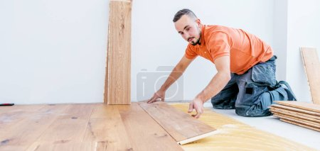 Photo for Worker installing parquet floor on construction site. Lay parquet floor - Royalty Free Image