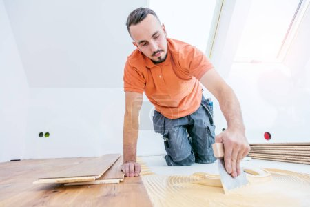 Photo for Male worker installing parquet floor on construction site. Lay parquet floor - Royalty Free Image