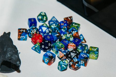 Dices for board games, dnd and rpg scattered on li...