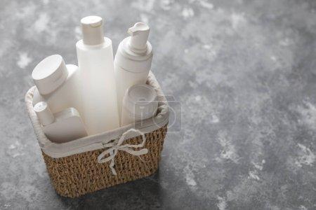 Photo pour Un panier rempli de bouteilles cosmétiques blanches en plastique sur fond gris avec de l'espace de photocopie - image libre de droit