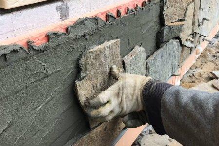 Photo pour Un constructeur fait face au sous-sol d'une maison avec une pierre sauvage. Appartement pour revêtement, tabata sur le chantier . - image libre de droit